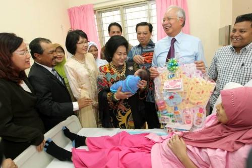 纳吉(右2)与夫人罗斯玛(左4)探访接生院,与產妇分享迎接新生命的喜悦,並送上礼篮祝贺。左起:王赛芝、加米基尔、李善如。右3:廖中莱。